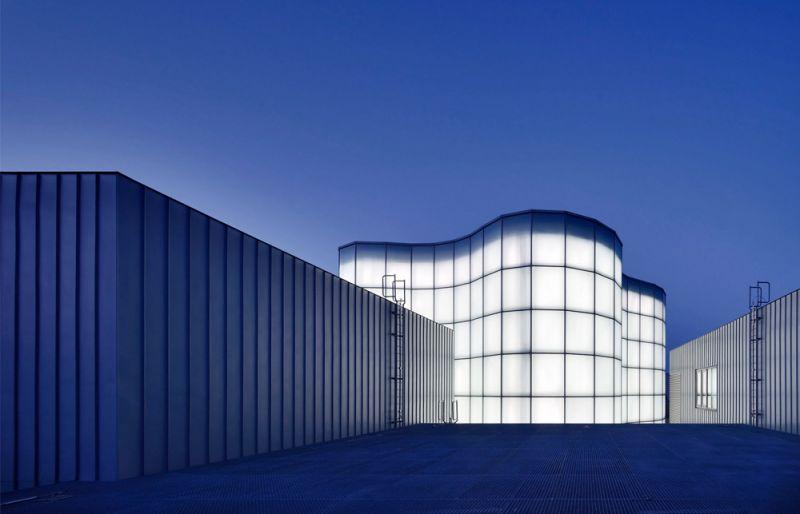 vista exterior nocturna de los volúmenes del edificio revestidos en zinc-titanio y atrio iluminado