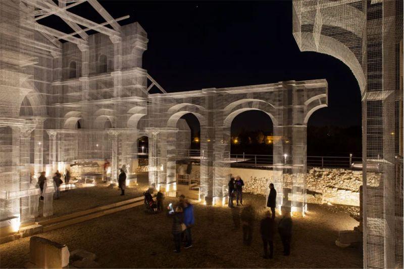 Imagen nocturna de la estructura metálica que reconstruye la basílica paleocristiana
