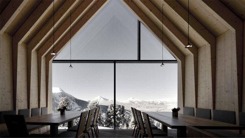 Imagen de una de las tres zonas de comedor del refugio y ventanal que mira hacia el paisaje