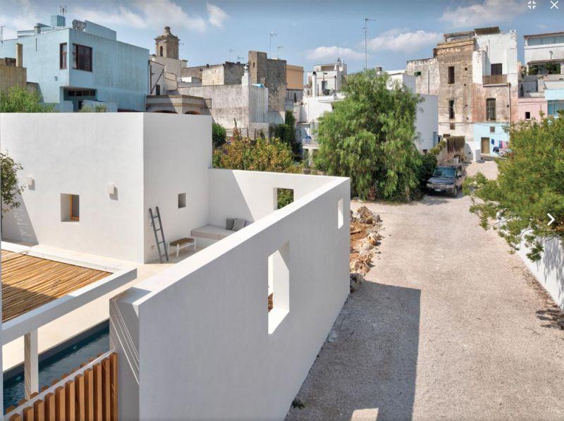 imagen de la parte del patio y el muro limítrofe con ventanas y el contexto urbano