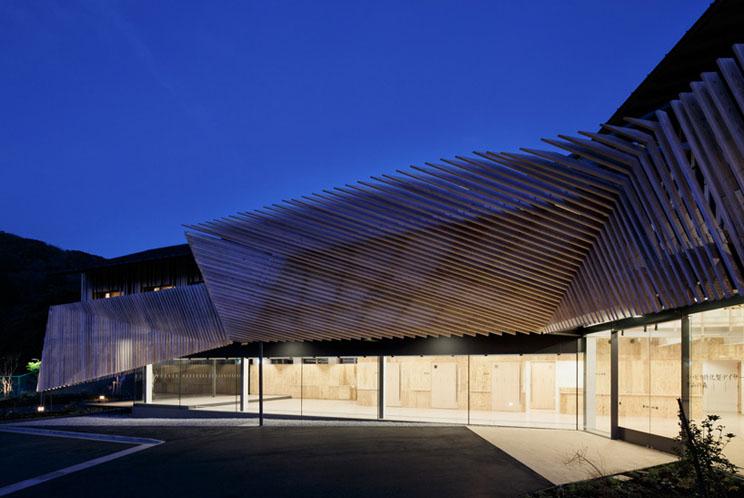 detrs de las lamas de madera de la fachada se encuentra la fachada de volmenes y luminosos